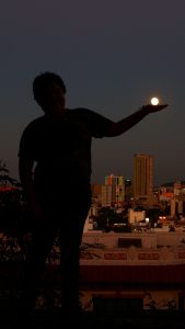 A silhouette of a boy in front of a cityscape, holding the moon in his hand.