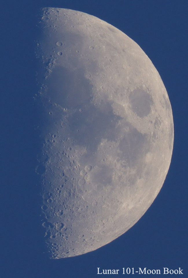 A moon just past 1st quarter, half its day side visible against a dark blue sky.