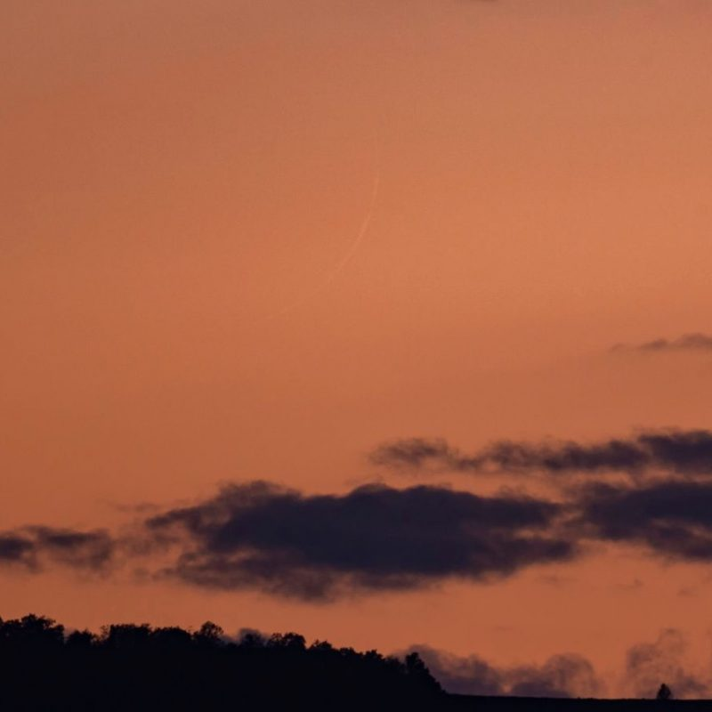 Extremely thin thread-like crescent moon in orange sky.