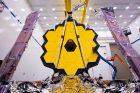 The James Webb Space Telescope displays its large and striking yellow sunshield with foldable structures surrounding it.