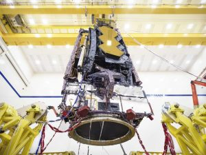 The James Webb Space Telescope in its fully-assembled position is lifted off the ground using local machinery.