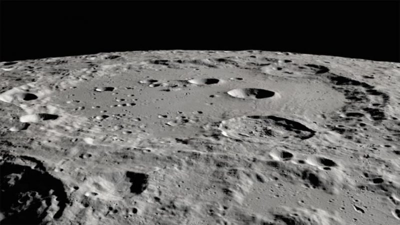 Oblique view of large crater with many small craters in and around it, with very black shadows at edges.
