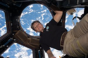 NASA Astronaut Peggy Whitson is seen floating in the ISS while Earth's ocean is covered by clouds just outside a window's view.
