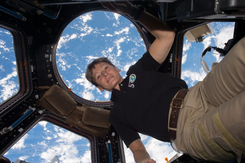 Woman floating in multi-windowed chamber of ISS with blue and white Earth visible through windows.