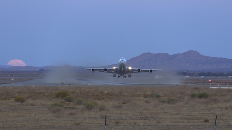 Large jet aircraft flying low, seconds after takeoff, in a desert landscape with mountains in the background and the moon rising.