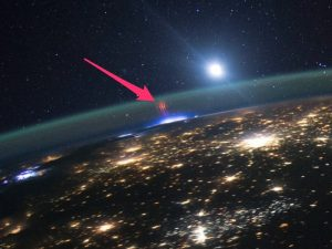 City lights on Earth with short red streaks above, and moon and stars in distance.