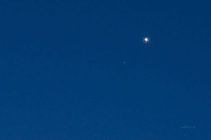 Bright planet Venus and fainter star Regulus., in a blue twilight sky.