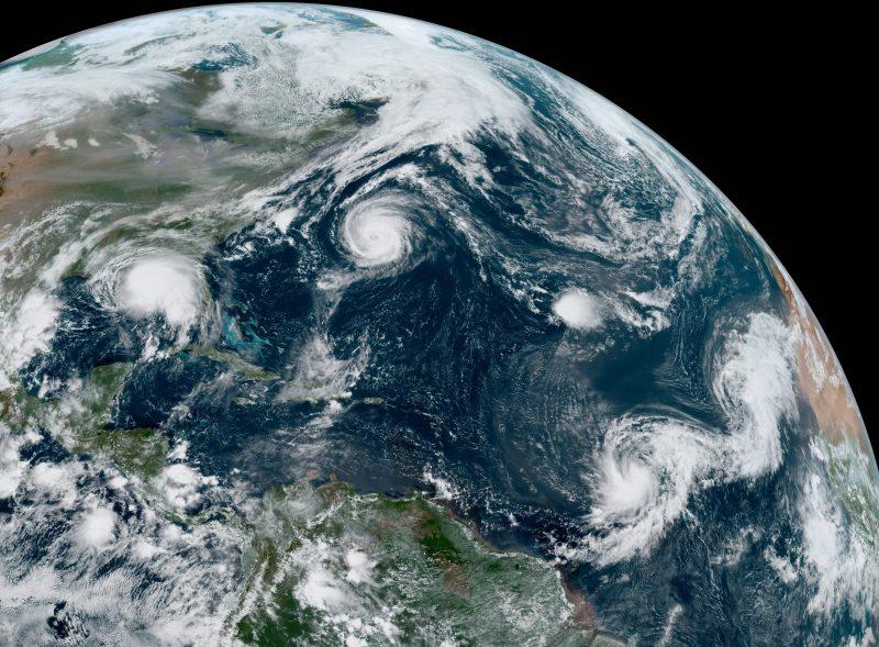 Satellite view of Atlantic Ocean showing 5 white circular tropical storms.