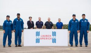 Crew-1 astronauts are seen posing for a photo with members of NASA administration and a banner that displays the Launch America logo.