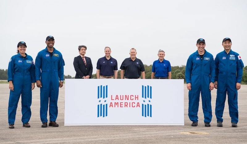 4 astronauts in blue flight suits with 4 men standing behind a banner with the Launch America logo