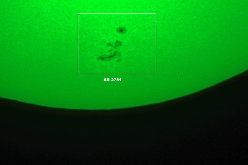 Green sun with closeup of dark spots surrounded by gray rims.