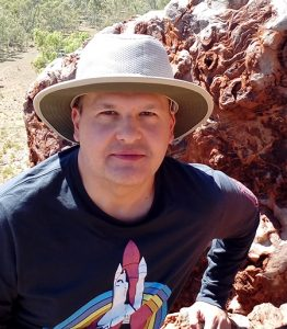 Man with hat and t-shirt with a rocket design on the front, and boulder in the background.