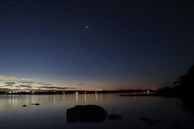 Two bright dots close together in dark blue twilight sky over body of water.