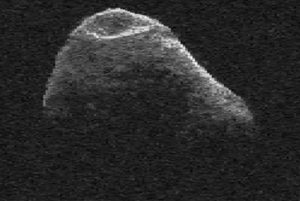 Irregular gray chunk of rock with large indentation, against black background.