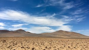 Desert with hills in distance and wispy clouds in blue sky above.