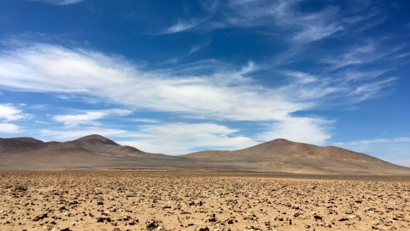 Flat, rocky desert with hills in distance and wispy clouds in blue sky above.