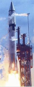 Rocket launch, flame and smoke, below a stocky white rocket.