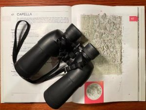 Binoculars on top of a map of the moon.