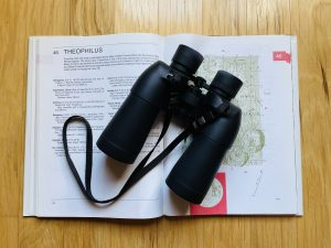 Binoculars rest on a map of the moon.