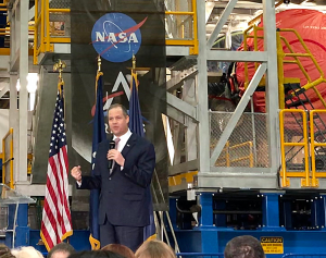 A man in a suit, standing under a NASA logo, and in front of a machine assembly.