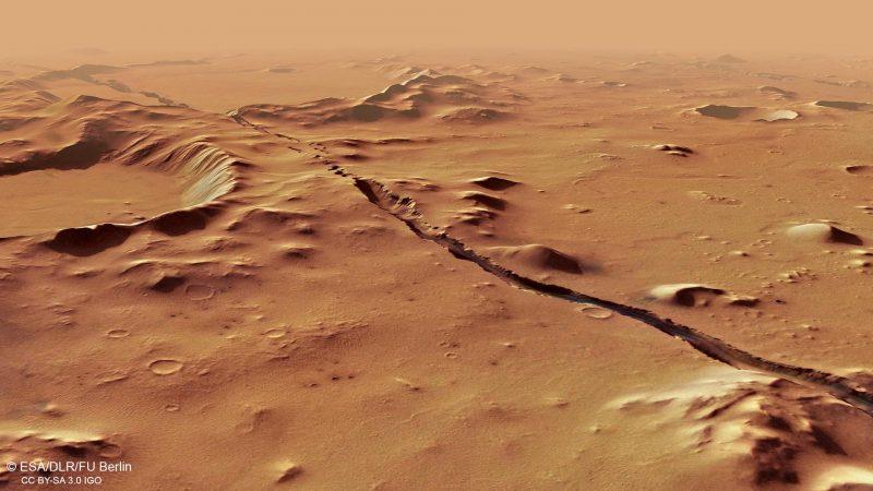 Long crack in reddish rocky terrain.