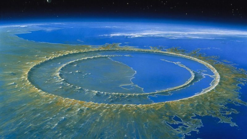 Oblique view of gigantic circular crater with two concentric rims, half filled with water from the adjacent sea.