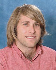 Smiling man against bluish mottled background.