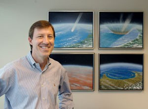 Smiling man with four framed paintings of the asteroid impact behind him on a wall.