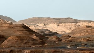 Layered hills and buttes with blue sky in background.
