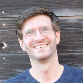 Smiling man in eyeglasses with wood paneling behind him.