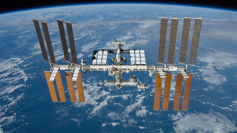 ISS in orbit: connected cylindrical modules and solar panel wings with Earth visible below.