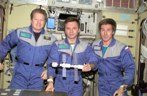 Expedition 1 crew members Bill Shepherd, Yuri Gidzenko, and Sergei Krikalev are seen posing with a small model of the International Space Station.