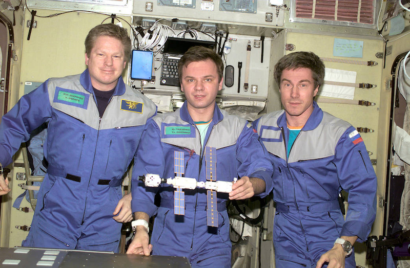 Three men in blue flight suits in a space station chamber, with a model with three modules.