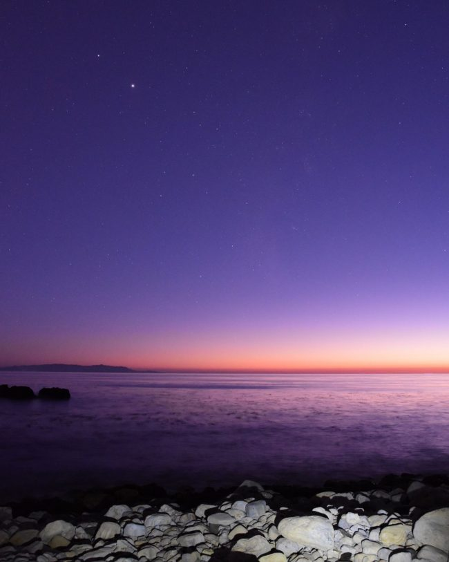 Jupiter and Saturn above sunset over calm water with small rocks in foreground.