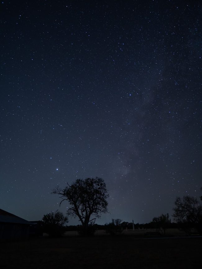 Jupiter, Saturn, Milky Way in starry sky over dark landscape with trees and barn.