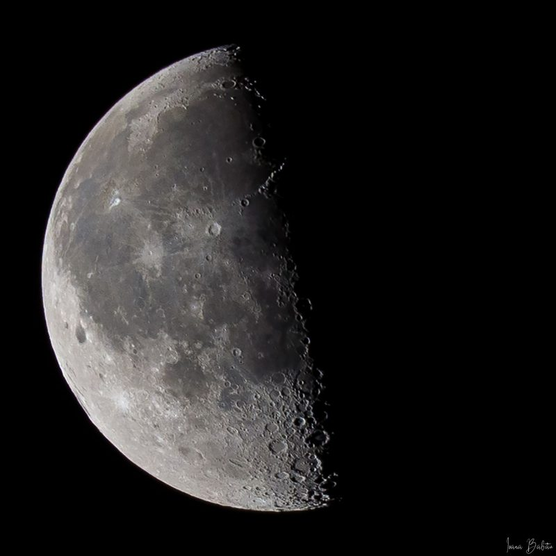 The moon with the left half visible and the right half lost in darkness.