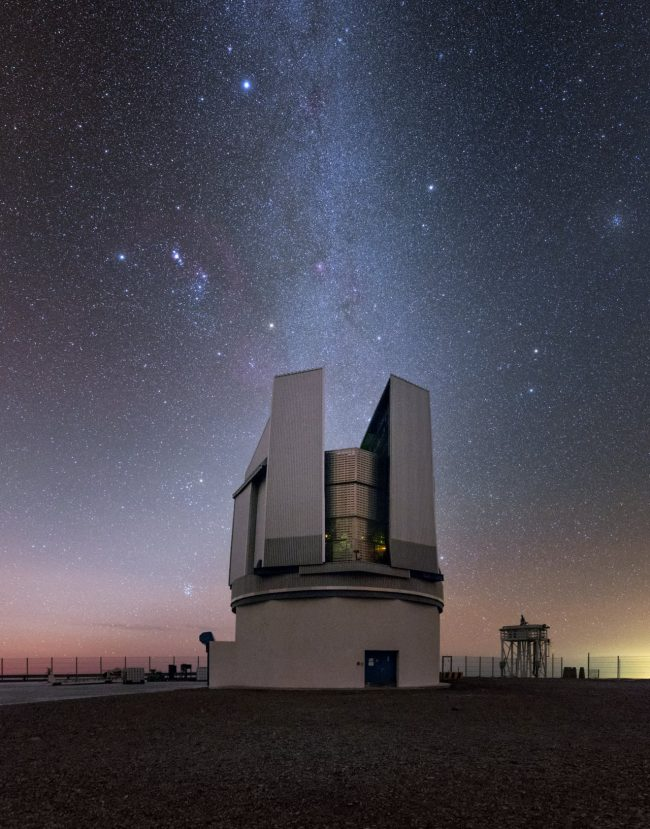 Orion hovers in starry sky above open observatory dome.