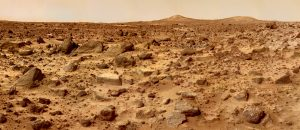 Rocky reddish terrain with two hills in the distance and dusty sky.
