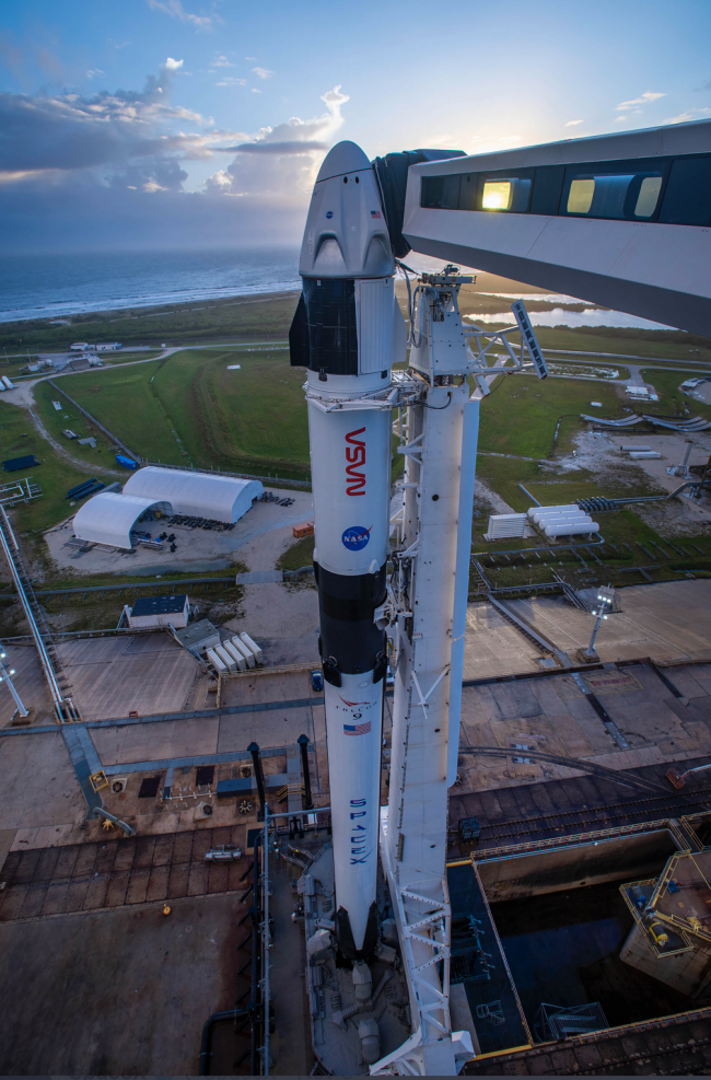 Tall white rocket standing on launch pad, viewed from above.