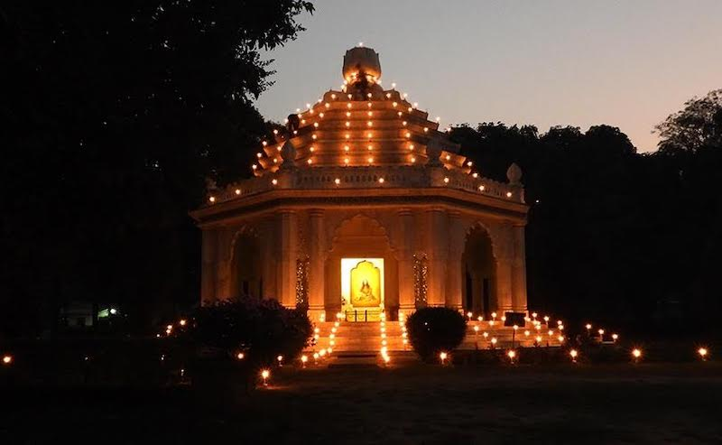 A domed temple with lights on the dome's ridges and surrounding it on the ground.