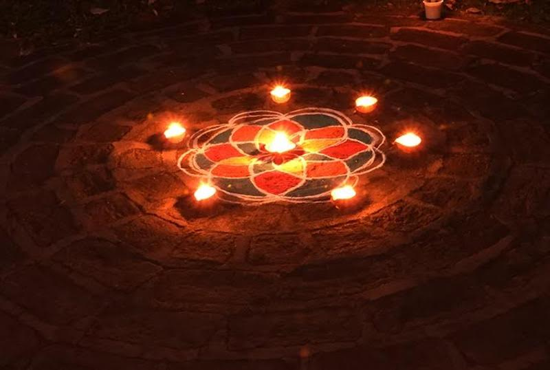 Six lights around a six-petaled design on the ground with a light in the middle.
