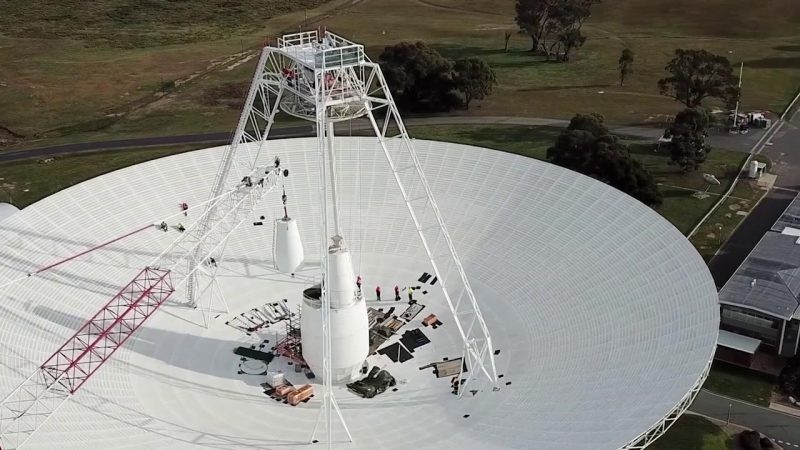 White dish-shaped antenna with receiver on struts above the center and a red crane on the left.
