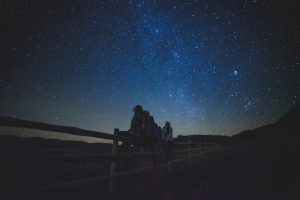 Children sit on a fence and gaze up at the stars.