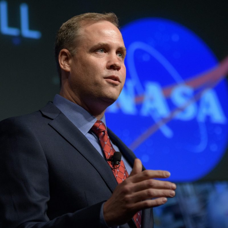 A man in a suit, next to a large NASA logo.