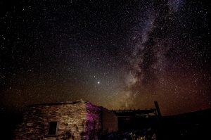 Jupiter, Saturn, Milky Way, above an abandoned building, under a dark desert night sky.