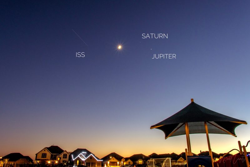 Jupiter, Saturn, the moon, and a streak - the ISS - in a twilight sky, above a suburban neighborhood.