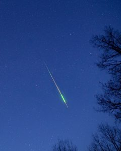 Bright colorful meteor against a bluish sky.