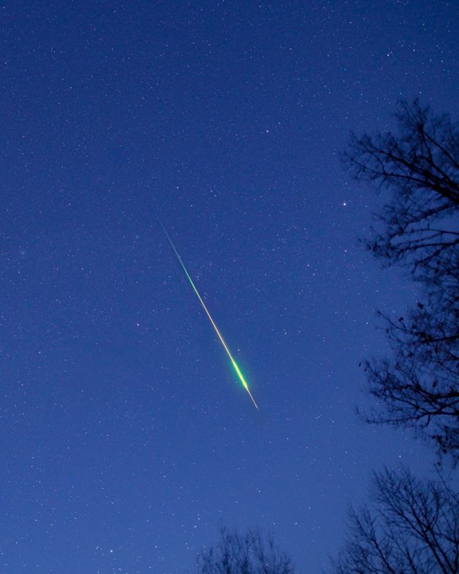 Long bright colorful meteor streak against a bluish sky.
