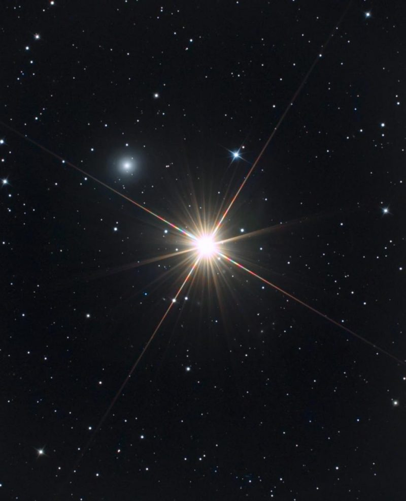Brilliant star with rays on star field with large fuzzy dot to upper left.