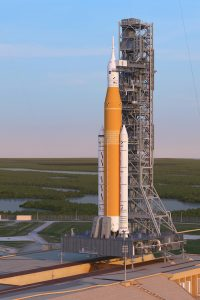 A tall orange rocket with 2 side boosters standing next to a launch tower.
